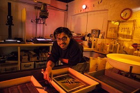 Photograph of a person in a photography darkroom.