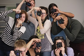 Photograph of a group of people holding cameras to their faces