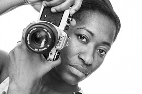A black and white photograph of a person holding an SLR camera near their face.