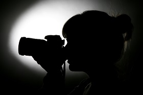 a silhouette of a girl taking a photograph with an SLR camera.