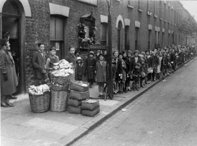 Waiting for 'farthing bundles' at the Fern Street Settlement, 1934